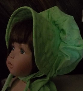 Fresh green baby bonnet with tiny kermit pattern