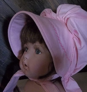 soft pink baby bonnet with darker pink scalloped embroidery